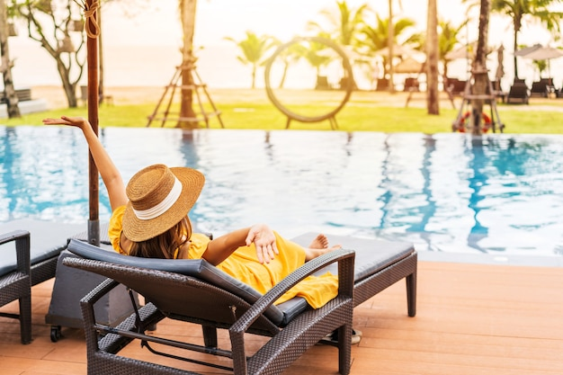 Jonge vrouw reiziger ontspannen en genieten van de zonsondergang bij een tropisch resort zwembad tijdens het reizen voor zomervakantie