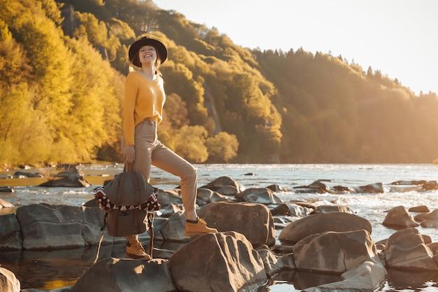 Jonge vrouw reiziger staan met rugzak op rivier natuur achtergrond
