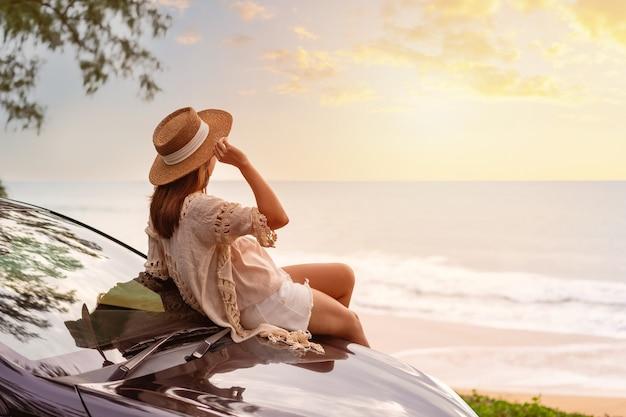 Jonge vrouw reiziger zittend op een auto en kijken naar een prachtige zonsondergang op het strand tijdens het rijden road trip op vakantie reizen