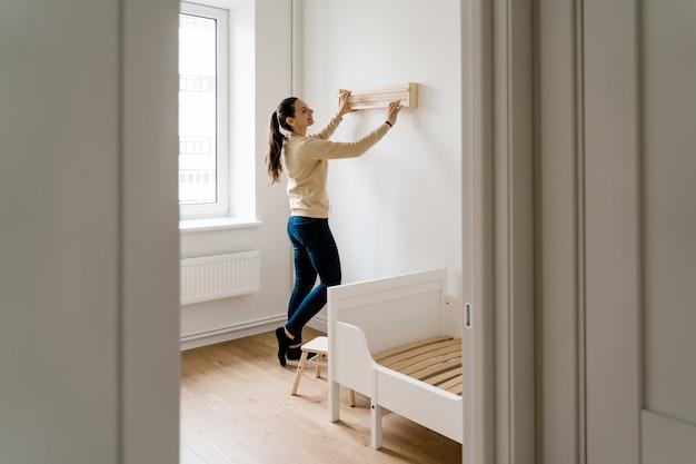 Jonge vrouw renovatie kind kamer in nieuw huis. houten boekenplank. neutrale kinderkamer