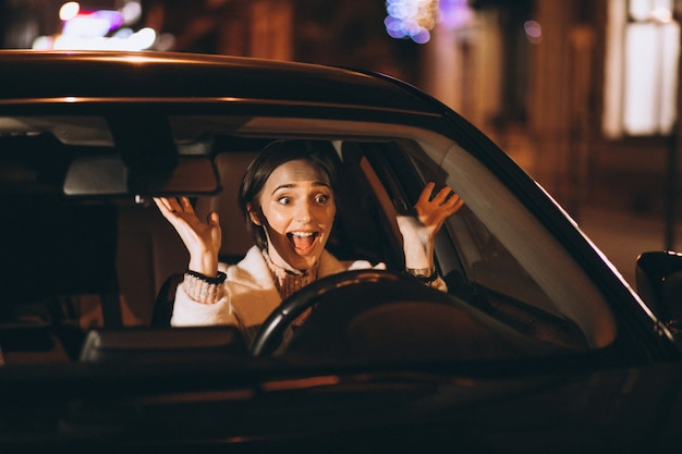 Jonge vrouw rijden in auto 's nachts