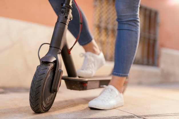 Jonge vrouw rijdt in een elektrische scooter in de stad