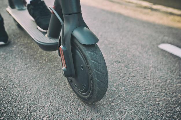 Jonge vrouw rijdt op een elektrische scooter door de stad 's avonds via paden