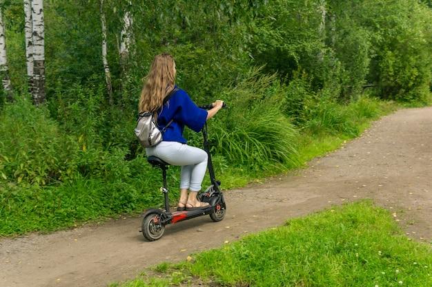 Jonge vrouw rijdt op een elektrische scooter langs het pad door het park