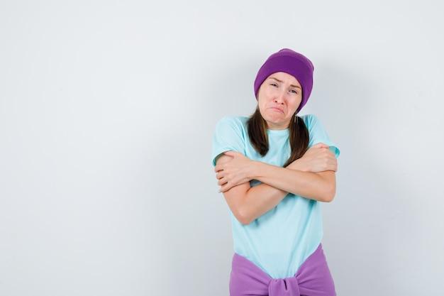 Jonge vrouw rillend van de kou in blauw t-shirt, paarse muts en uitgeput op zoek. vooraanzicht.