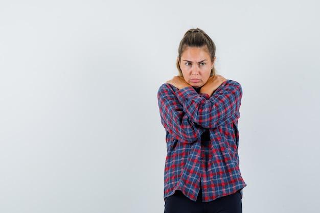 Jonge vrouw rilt van de kou in geruit overhemd en ziet er mooi uit