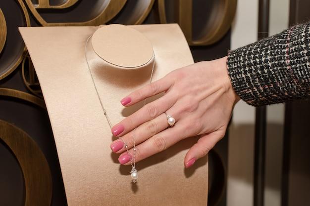 Jonge vrouw ring in juwelier kiezen. hand van vrouwelijke klant in juwelierszaak. een diamanten ring proberen met witte parel, mode en koopconcept.