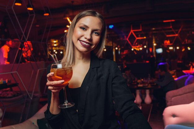Jonge vrouw rode zoete drank nippen in staaf