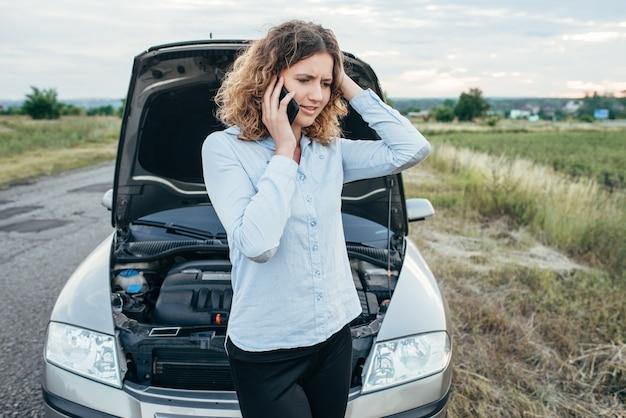 Jonge vrouw roept naar hulpdienst, kapotte auto. problemen met het voertuig op de weg op zomerdag