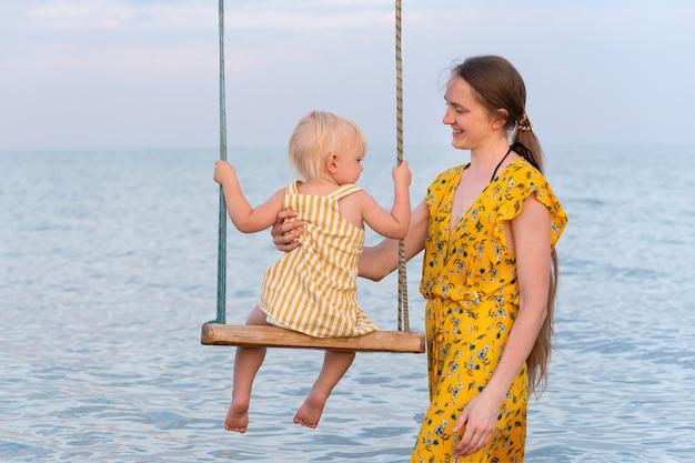 Jonge vrouw rolt baby op een schommel met uitzicht op de zee. vakantie op zee met kinderen.