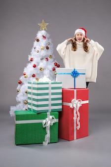 Jonge vrouw rond cadeautjes op grijs