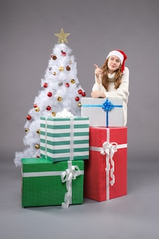 Jonge vrouw rond kerstcadeautjes op grijs