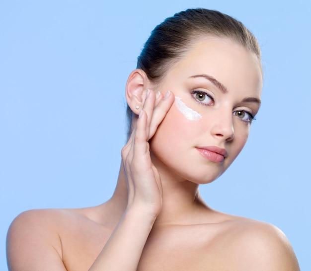 Jonge vrouw room toe te passen op haar gezicht op blauw
