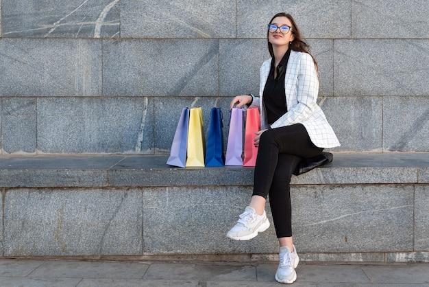 Jonge vrouw rust op bankje in de stad na succesvol winkelen.