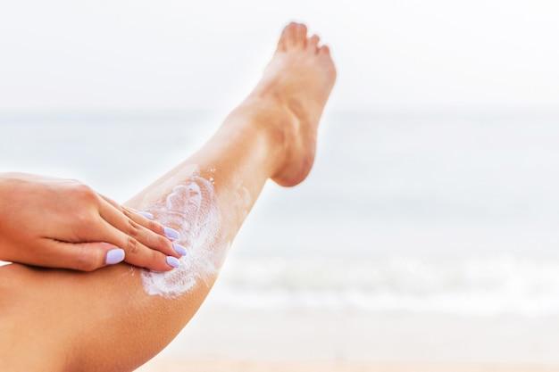 Jonge vrouw rust op de zonnebank op het strand en beschermt haar huid door sunblock op haar been toe te passen.