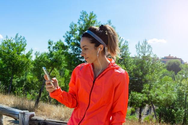 Jonge vrouw rust terwijl ze naar haar resultaten op een smartphone kijkt na een gezonde levensstijl