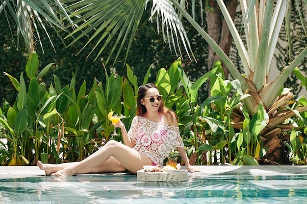 Jonge vrouw rusten bij zwembad