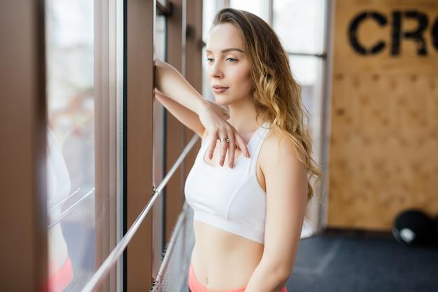Jonge vrouw rusten na training bij sportschool. fitness vrouw pauze na trainingssessie in gezondheidsclub.