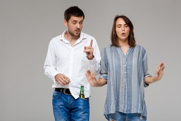 Jonge vrouw ruzie, boos met dronken man over grijze muur