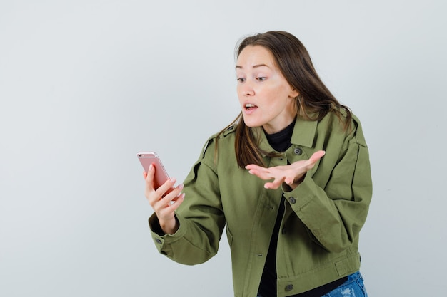 Jonge vrouw ruzie met iemand tijdens videogesprek in groene jas, vooraanzicht.