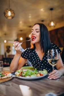 Jonge vrouw salade eten in een café