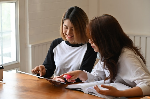 Jonge vrouw samen en tutor met boek en tablet op tafel.