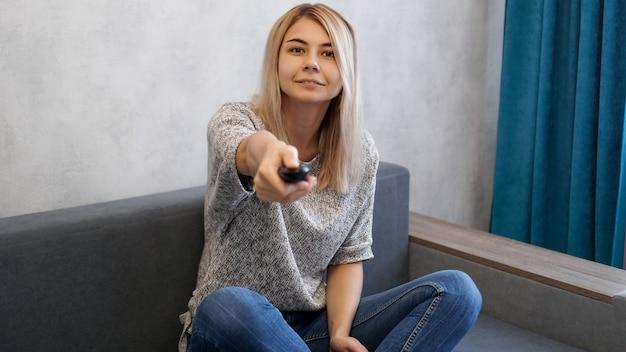 Jonge vrouw schakelt de televisiekanalen met de afstandsbediening. ze lacht en kijkt naar de camera