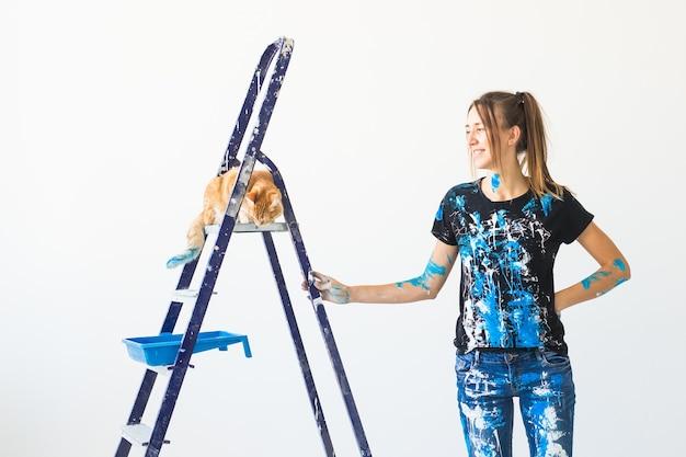 Jonge vrouw schilder, ontwerper en werknemer schildert de muur. de kat zit vervolgens op de ladder en kijkt naar het werk.