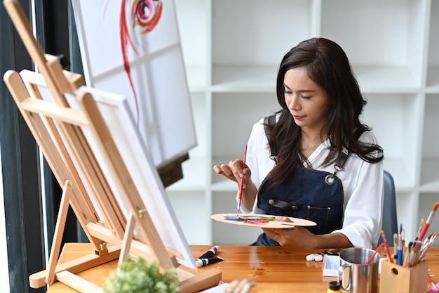 Jonge vrouw schilderij foto met water kleur op haar kunstatelier.