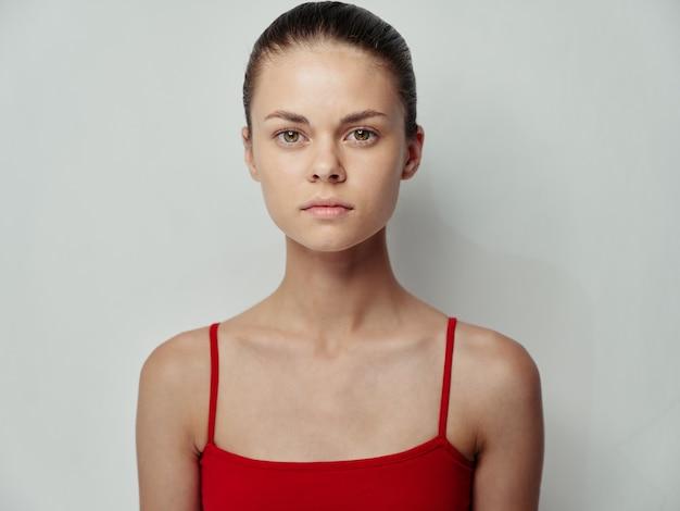 Jonge vrouw schone huid cosmetologie rode tshirt lichte achtergrond model