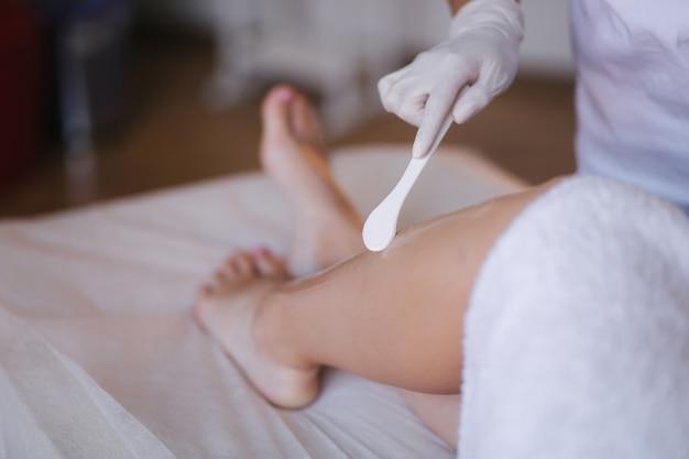 Jonge vrouw schoonheidsspecialiste in masker geldt contactgel op het been van een vrouw voor laser ontharing in medische kliniek. detailopname