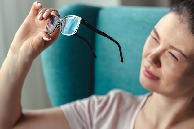 Jonge vrouw schoonmaak bril met een servet zittend in een ch