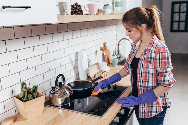 Jonge vrouw schoonmaak oven in de keuken.