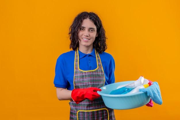 Jonge vrouw schort dragen en rubberen handschoenen die bassin met schoonmakende hulpmiddelen houden kijkend zeker glimlachend vrolijk over oranje muur