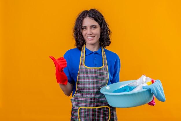 Jonge vrouw schort dragen en rubberhandschoenen die bassin met schoonmakende hulpmiddelen die met grote glimlach op gezicht houden die duimen over oranje muur tonen