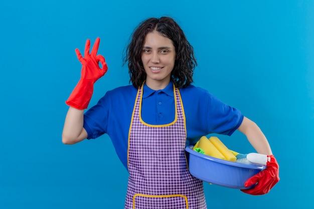 Jonge vrouw schort dragen en rubberhandschoenen die bassin met schoonmakende hulpmiddelen houden glimlachend vriendschappelijk doend ok teken over blauwe muur