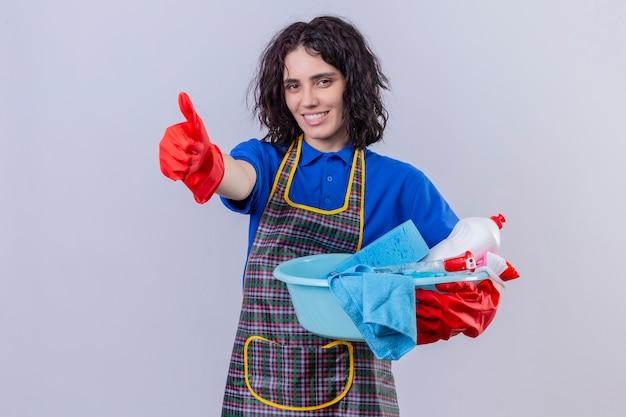 Jonge vrouw schort dragen en rubberhandschoenen die bassin met schoonmakende hulpmiddelen met grote glimlach op gezicht houden die duimen over witte muur tonen