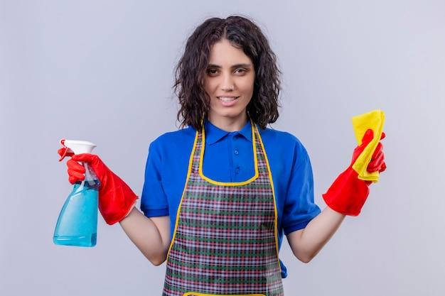 Jonge vrouw schort dragen en rubberhandschoenen die deken houden en nevel die met glimlach op gezicht over witte muur schoonmaken