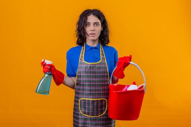 Jonge vrouw schort dragen en rubberhandschoenen die emmer met schoonmakende hulpmiddelen houden en nevel schoonmaken die verward over oranje muur kijken die