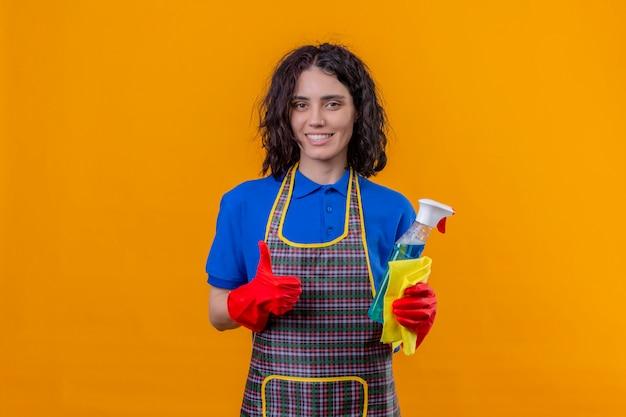 Jonge vrouw schort dragen en rubberhandschoenen die schoonmakende nevel en deken met grote glimlach op gezicht houden die duimen over oranje muur tonen