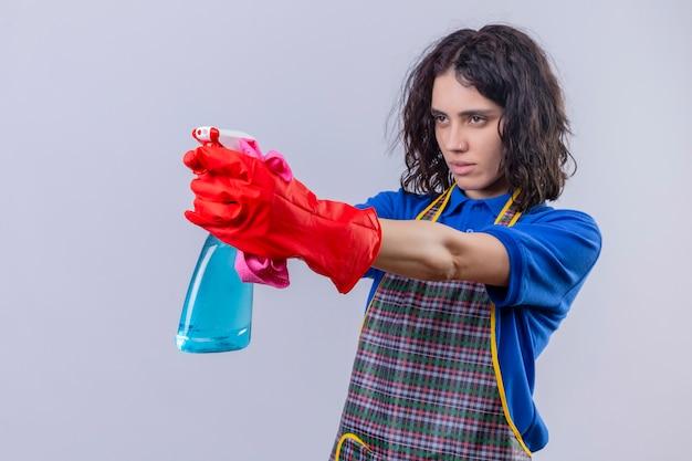 Jonge vrouw schort dragen en rubberhandschoenen die schoonmakende nevel houden gebruikend als kanon, klaar om over witte muur schoon te maken