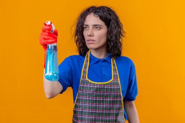 Jonge vrouw schort dragen en rubberhandschoenen die schoonmakende nevel houden kijkend opzij met ernstig gezicht, klaar om over oranje muur schoon te maken