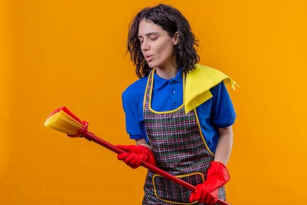 Jonge vrouw schort dragen en rubberhandschoenen die zwabber houden gebruikend als microfoon zingend een lied, hebbend pret over oranje muur