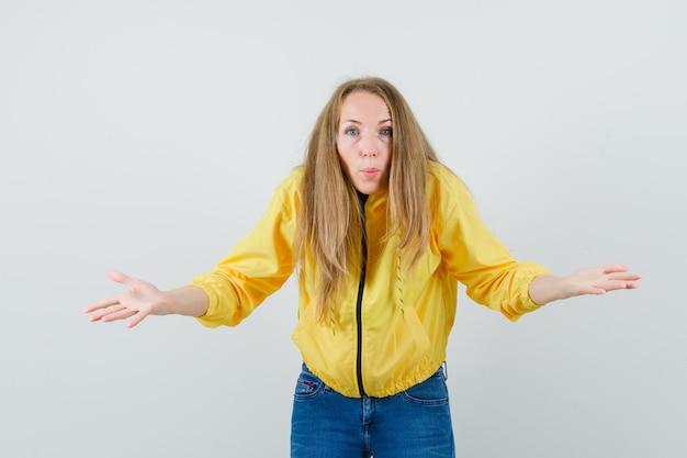 Jonge vrouw schouders ophalen in geel bomberjack en blauwe jean en onzeker op zoek. vooraanzicht.