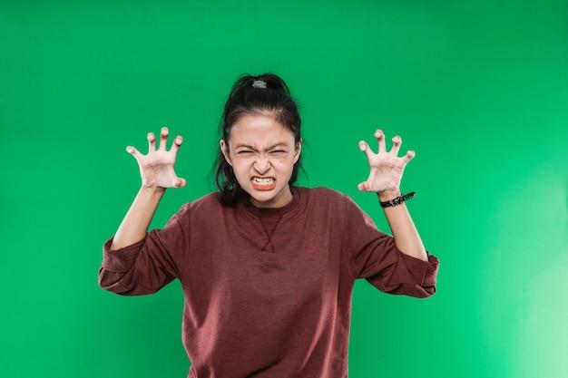 Jonge vrouw schreeuwen in paniek of woede, geschokt, doodsbang of woedend, met de handen naast het hoofd tegen op groene achtergrond