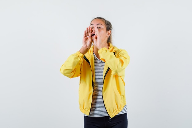Jonge vrouw schreeuwen of iets in jasje, t-shirt vooraanzicht aankondigen.