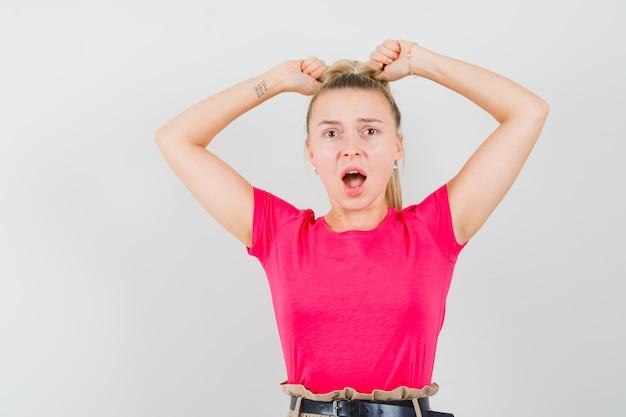 Jonge vrouw schreeuwen terwijl het trekken van haren in t-shirt en broek