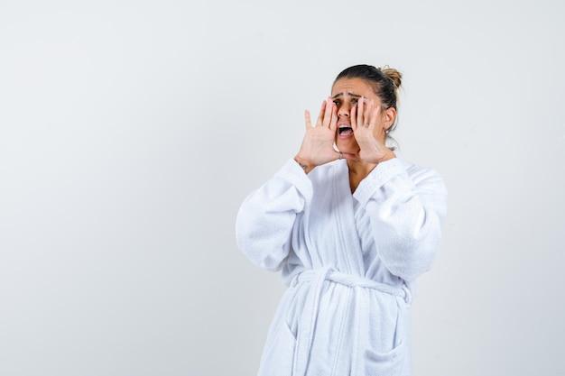 Jonge vrouw schreeuwt iets in badjas en kijkt bezorgd