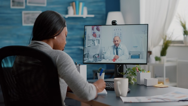 Jonge vrouw schrijft behandeling van luchtwegaandoeningen op notebook, bespreekt pillen en behandeling tijdens online videogesprek in de gezondheidszorg