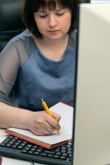 Jonge vrouw schrijft in notitieblok op de werkplek. secretaresse aan het werk. taakbeheer. taken plannen.